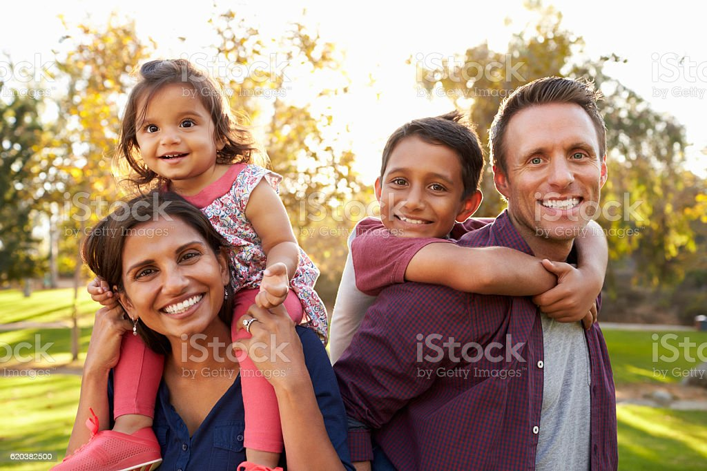 Mixed race parents carry their kids piggyback in a park stock photo