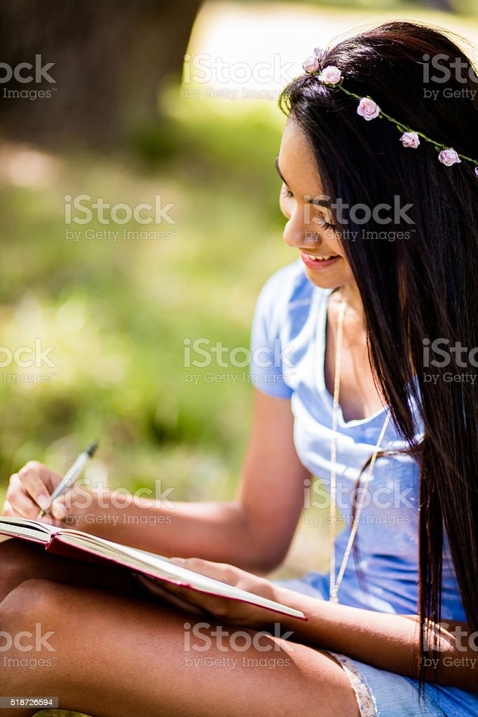 Mixed Race Person sitting at tree writing in journal stock photo