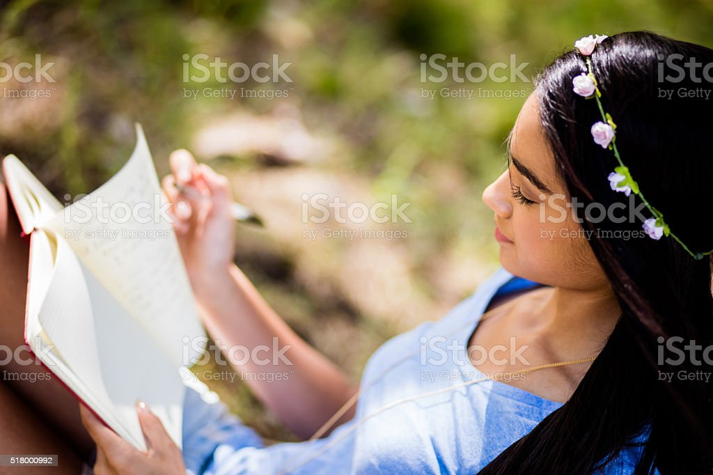 Mixed Race Person sitting outside writing in journal stock photo