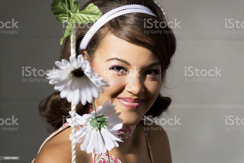 Mixed race teen with 60s hair peeking behind fake daisies. royalty-free stock photo