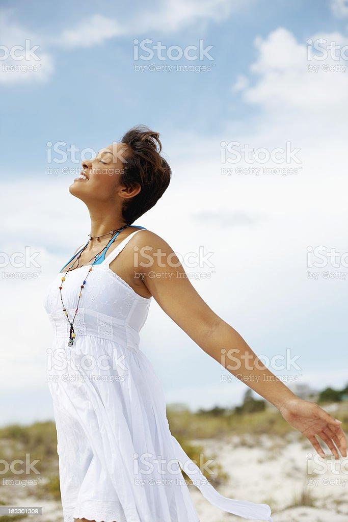 Mixed race woman enjoying the fresh air on beach royalty-free stock photo