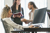Mixed race woman in office using computer