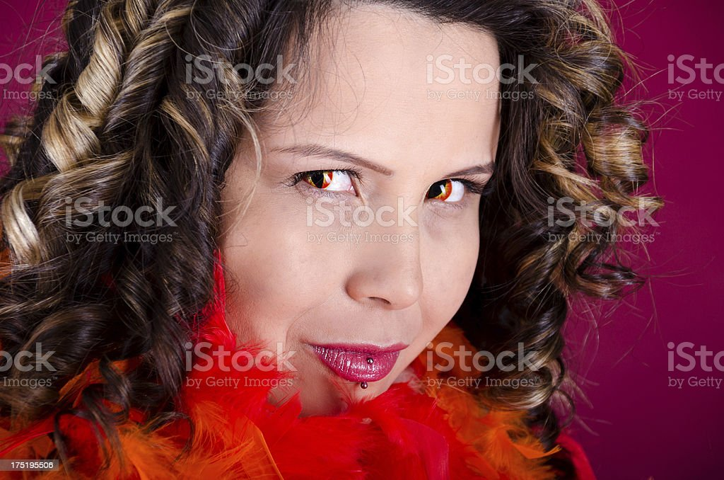 Mixed race woman in snake contacts smiling flirtatiously. stock photo