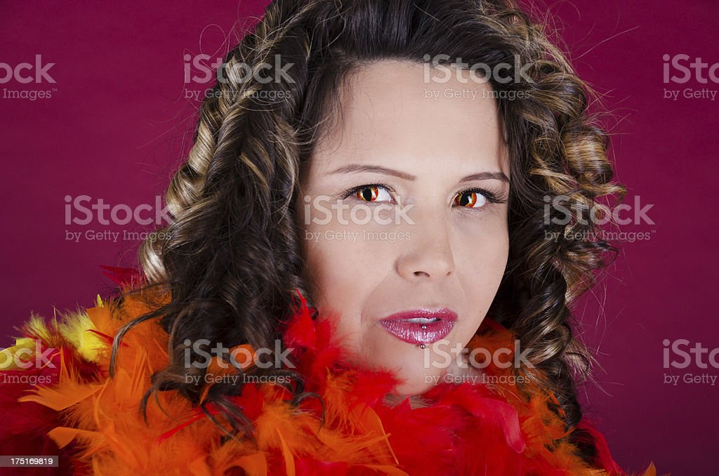 Mixed race woman in snake eye contacts and feathers. stock photo
