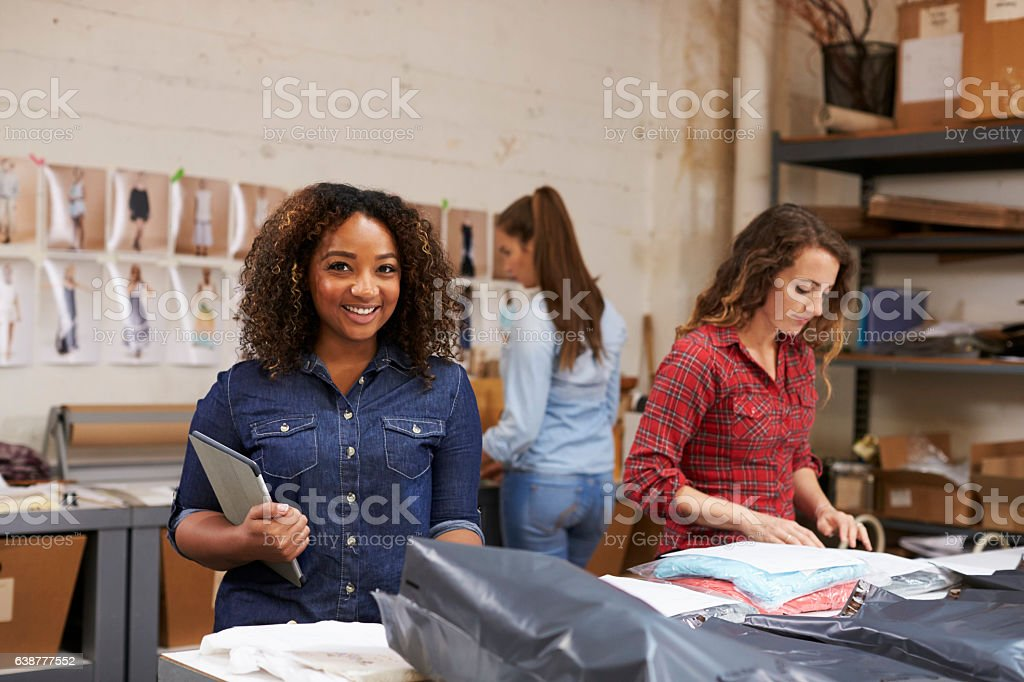 Mixed race woman packing clothing orders smiles to camera stock photo