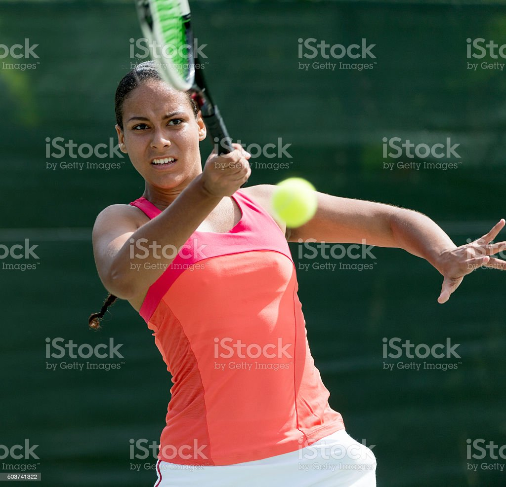 Mixed race Woman Playing Tennis stock photo