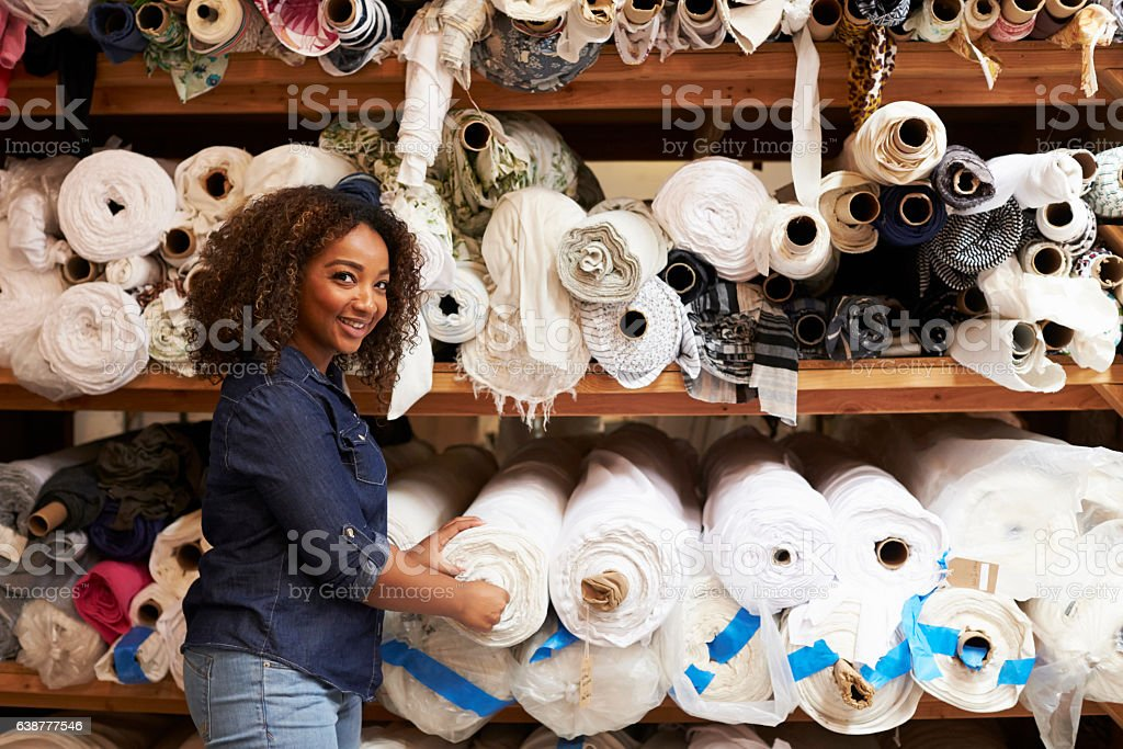 Mixed race woman selecting fabrics looking to camera stock photo