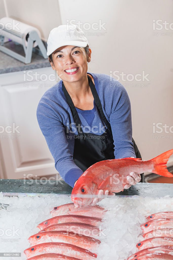 Mixed race woman working in fish market, holding snapper stock photo