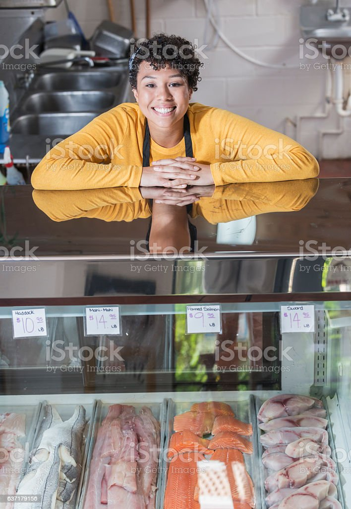 Mixed race woman working in fish market stock photo