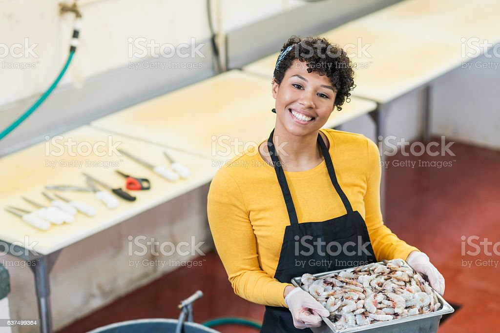 Mixed race woman working in fish market with shrimp tray stock photo