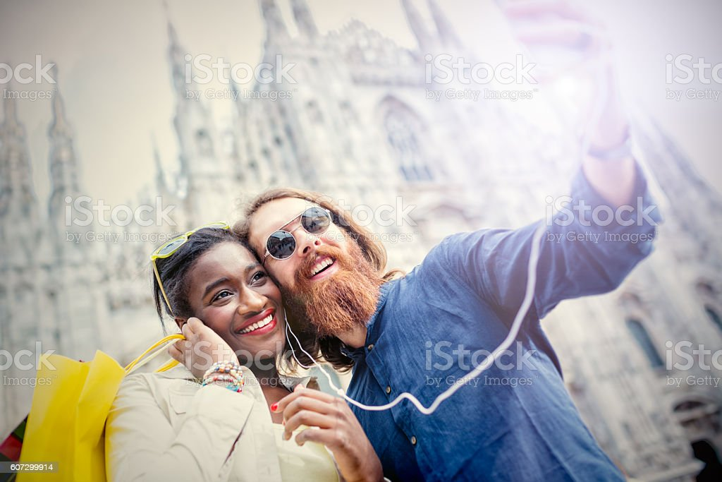 Mixed race young cool couple taking selfie at Duomo Square stock photo