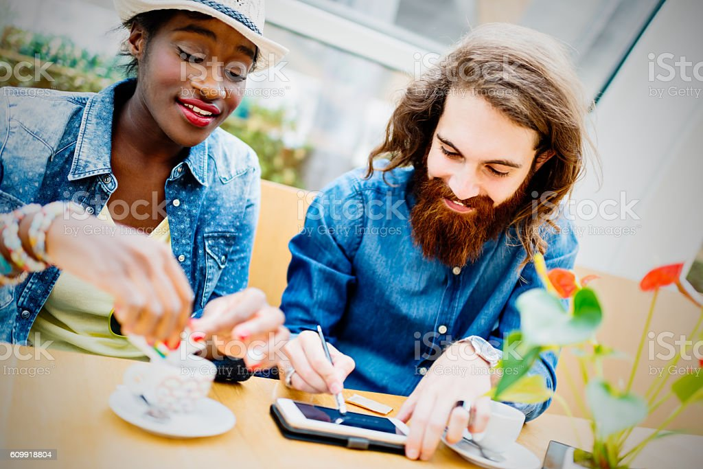 Mixed race young couple in sidewalk cafe stock photo