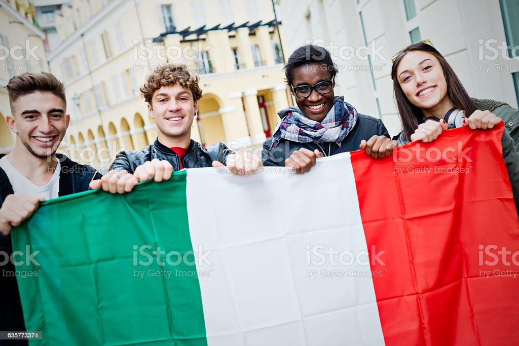 Mixed race young friends holding Italian flag stock photo