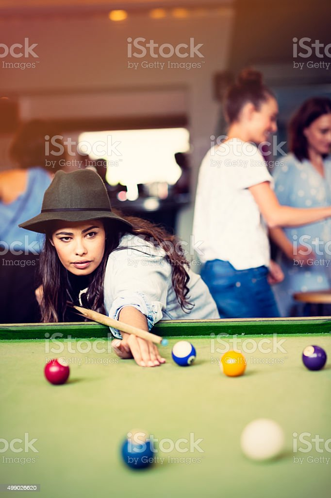 Mixed race young woman playing pool game in pub stock photo