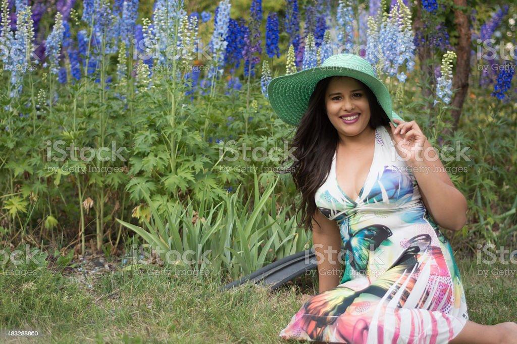 Mixed race young woman sitting in urban summer garden, horizontal. stock photo