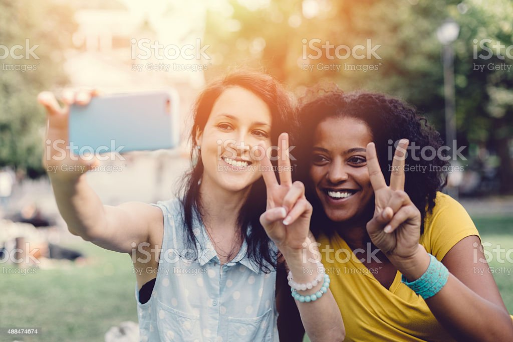 Mixed raced girls taking a selfie together stock photo