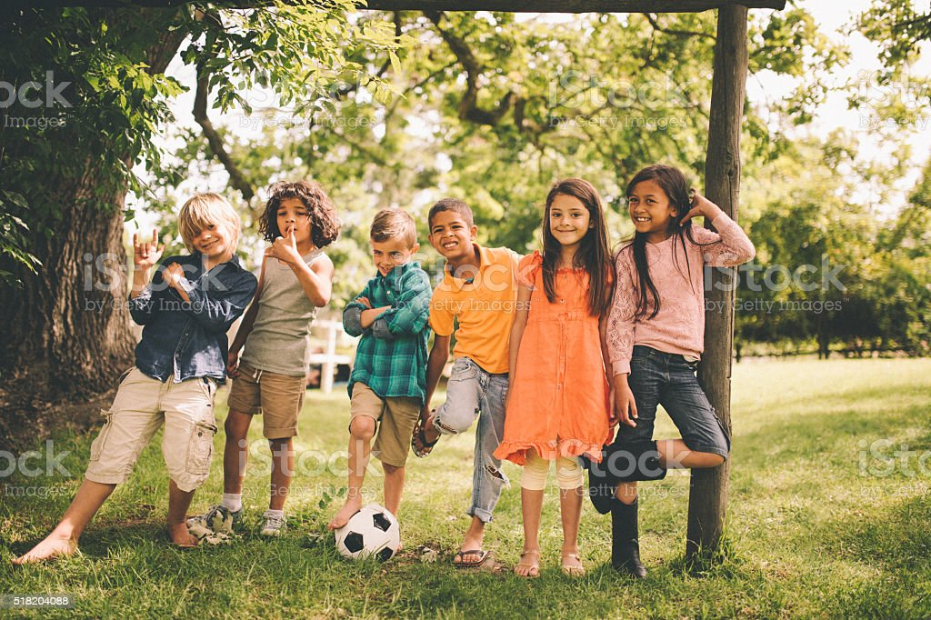 Mixed racial group of boys and girls with soccer ball stock photo