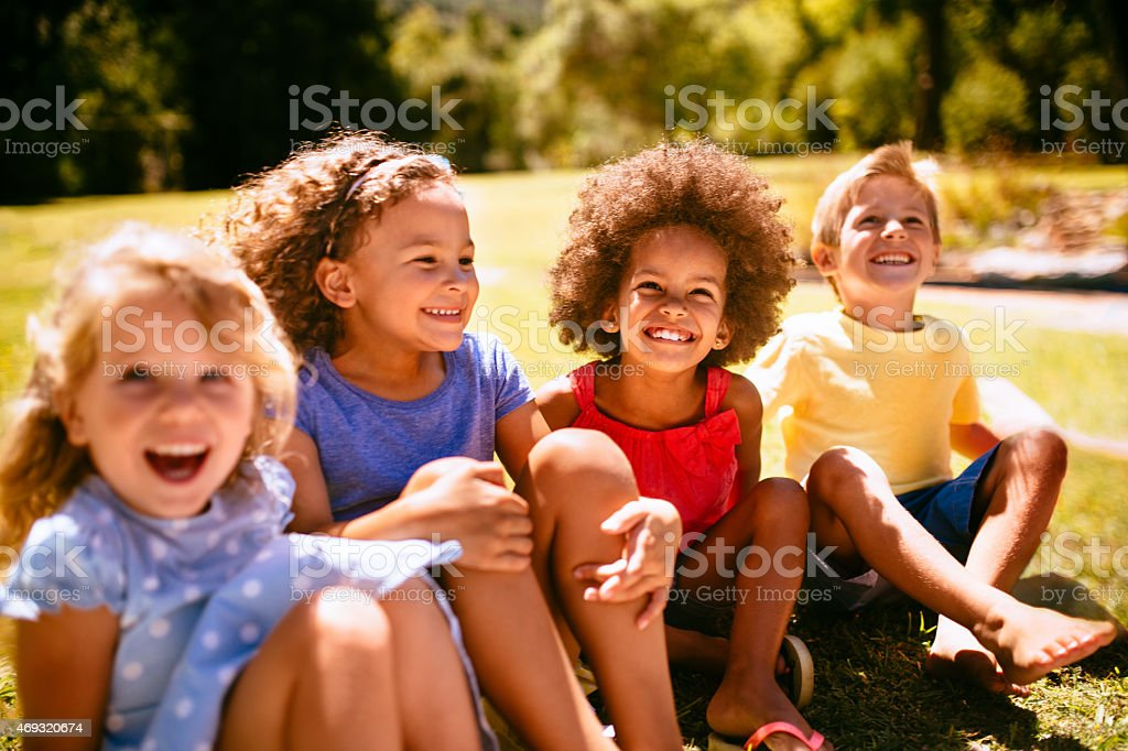 Mixed racial group of friendly children laughing together stock photo