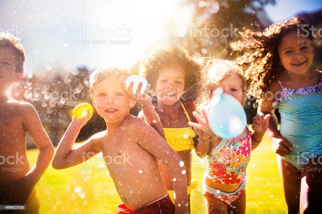 Mixed racial group of kids throwing water balloons at camera stock photo