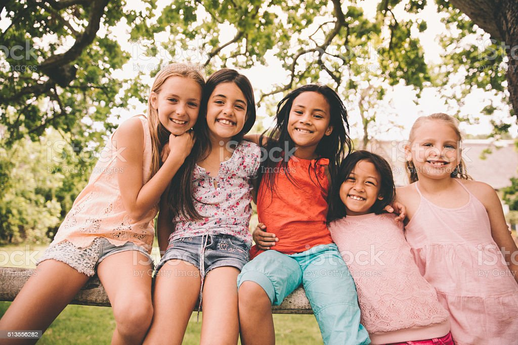 Mixed racial group of little girls smiling together in park stock photo