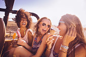 Mixed racial group of teens laughing with ice creams