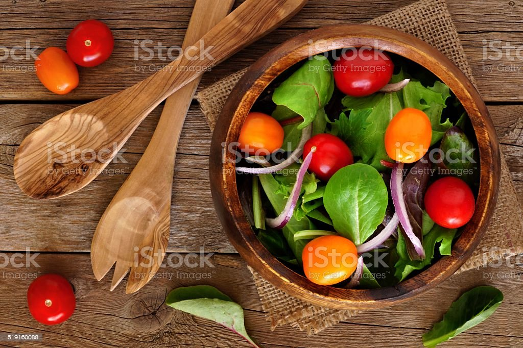 Mixed salad in wooden bowl overhead scene on rustic wood stock photo