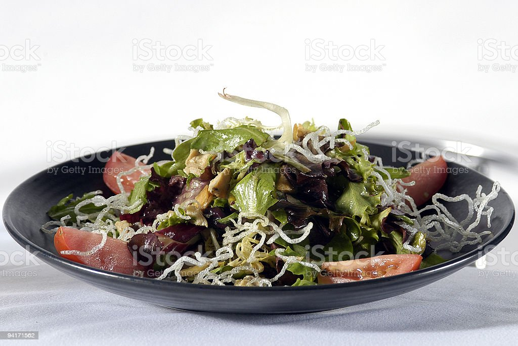 Mixed salad with noodles and tomato in black bowl royalty-free stock photo