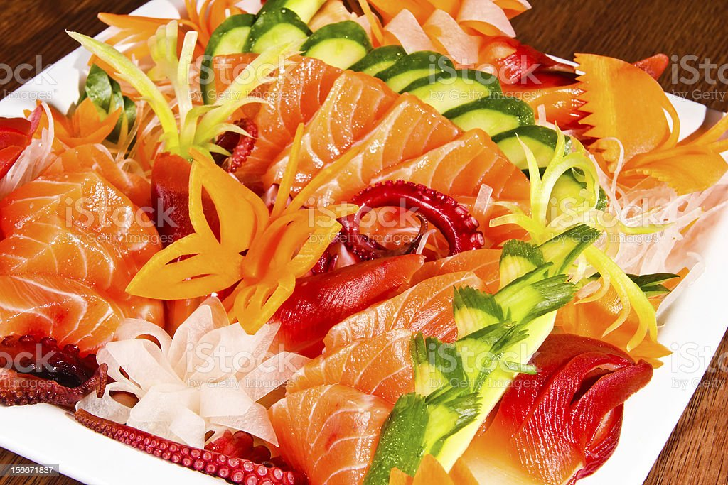 Mixed sashimi in white plate on wood table stock photo