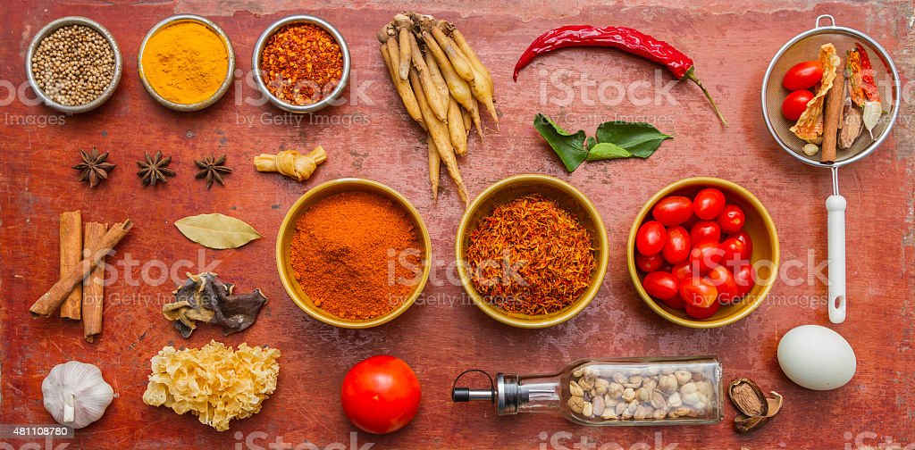 Mixed spices and herbs on red background. stock photo