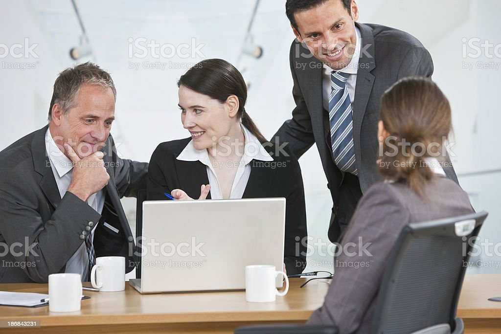 mixedrace business team working on laptop royalty-free stock photo