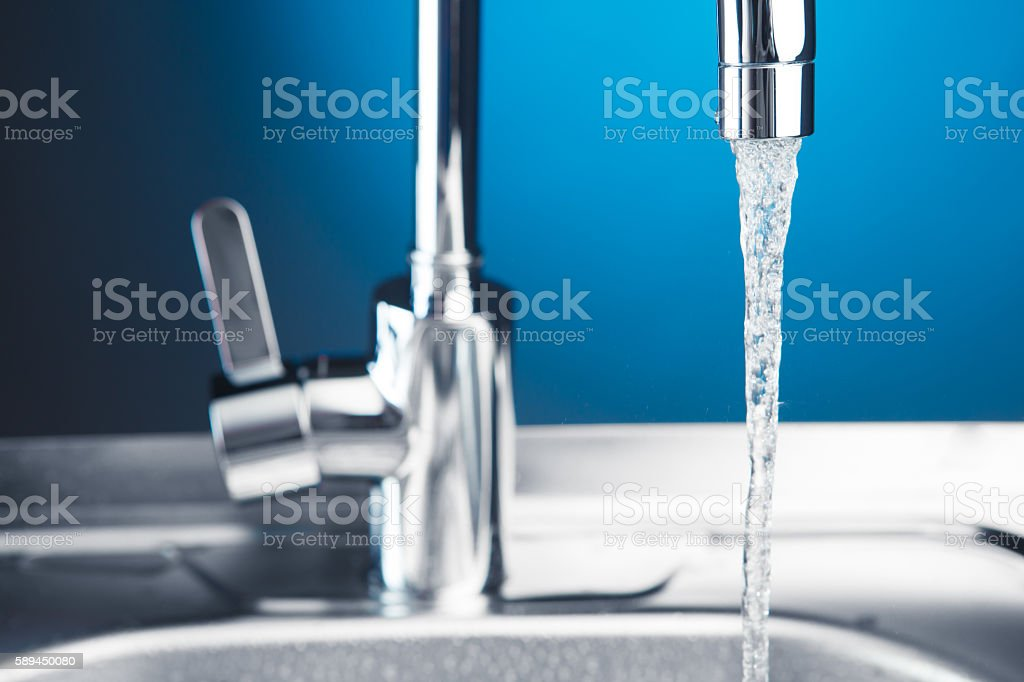 mixer tap with flowing water, closeup view stock photo