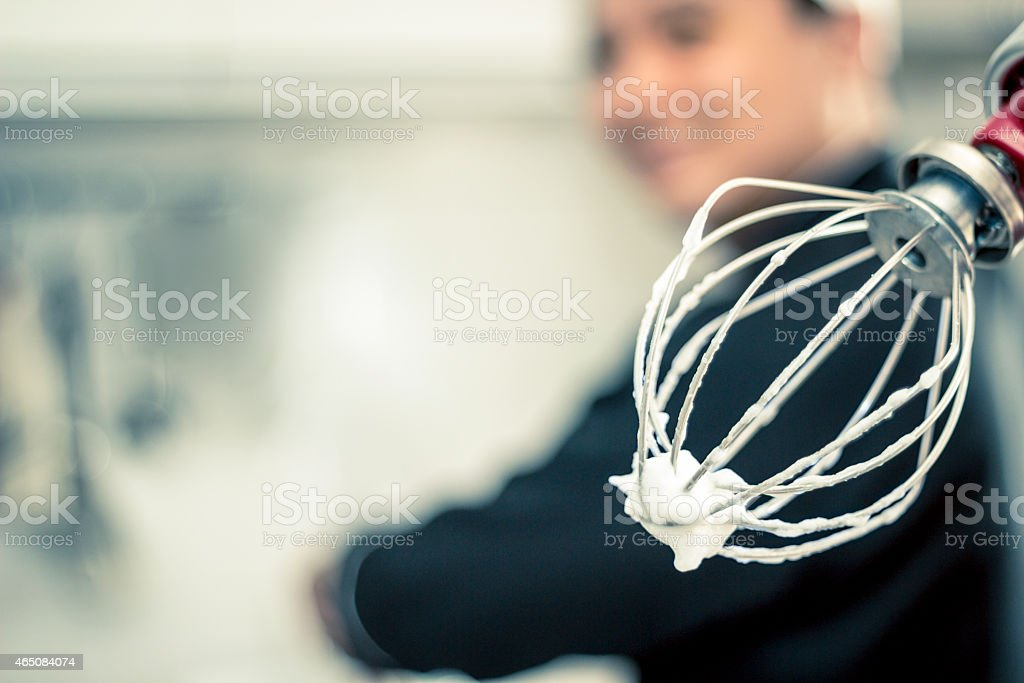 Mixer with egg whites and chef in blurred background. stock photo
