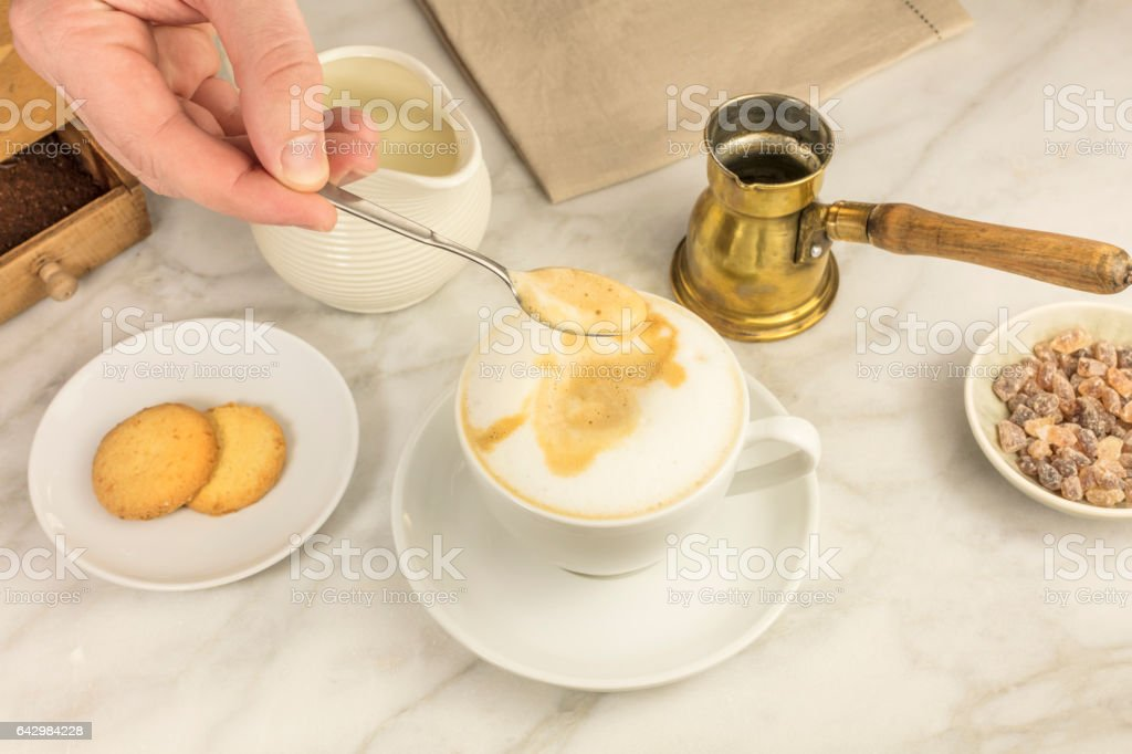 Mixing milk and coffee with spoon stock photo