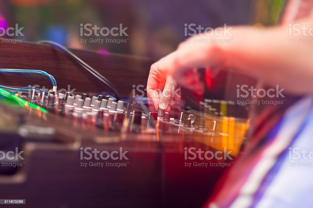 DJ mixing music on console at the night club stock photo