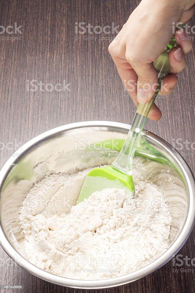 Mixing wheat flour in metallic bowl royalty-free stock photo
