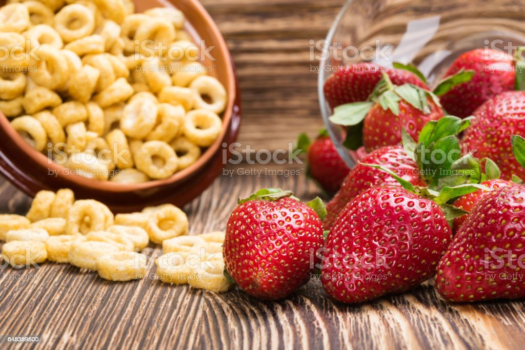 mixture of strawberry and corn flakes on a dark background stock photo