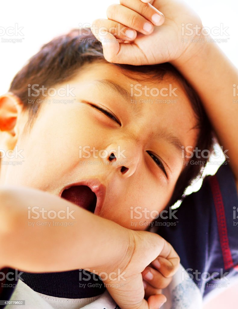 Moaning and arm stretching little thai boy stock photo