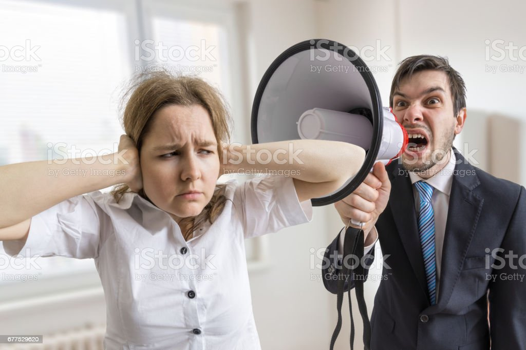 Mobbing at work. Manager is shouting at his secretary at work with megaphone. stock photo