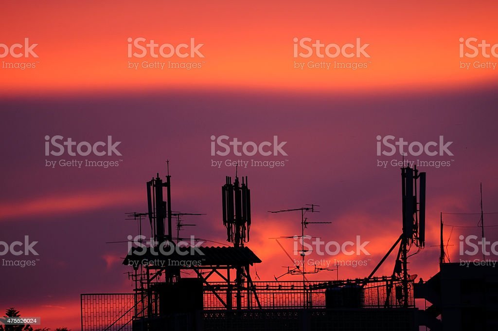 Mobile 3G network pole on top building during sunset time stock photo