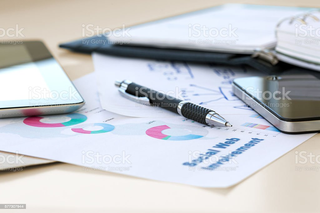 Mobile Business Thumb with Papers and digital Gadgets stock photo