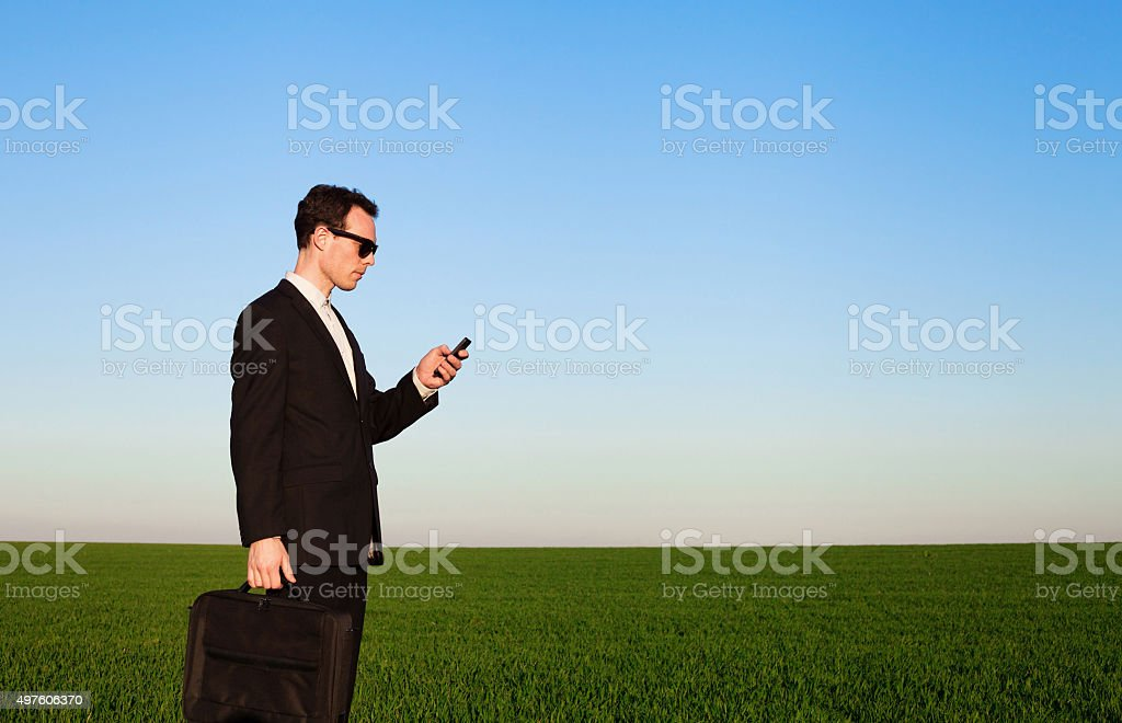 mobile connection, business man with phone in the field stock photo