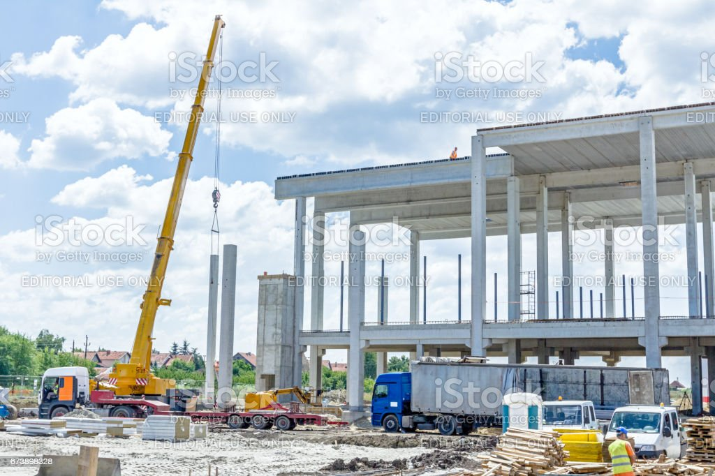 Mobile crane is carry concrete joist to assembly huge hall. stock photo