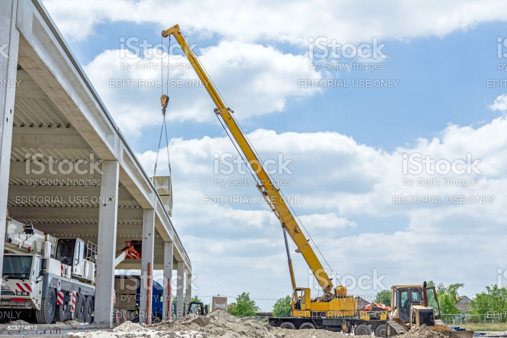 Mobile crane is raising package of glass wool on the roof huge unfinished hall stock photo