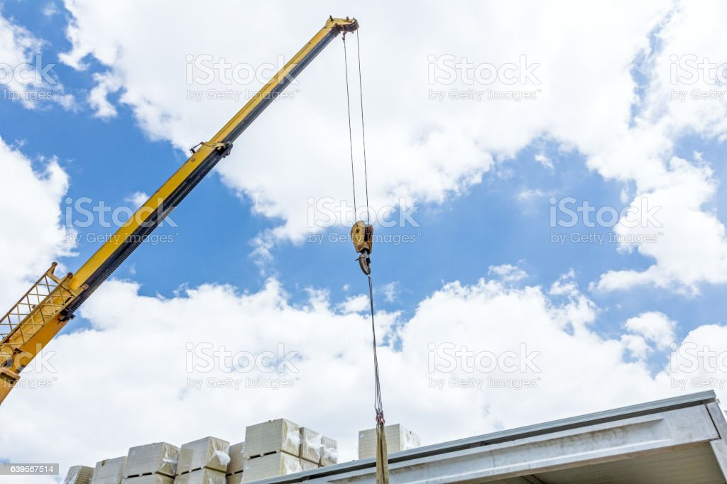 Mobile crane is raising package of glass wool. stock photo