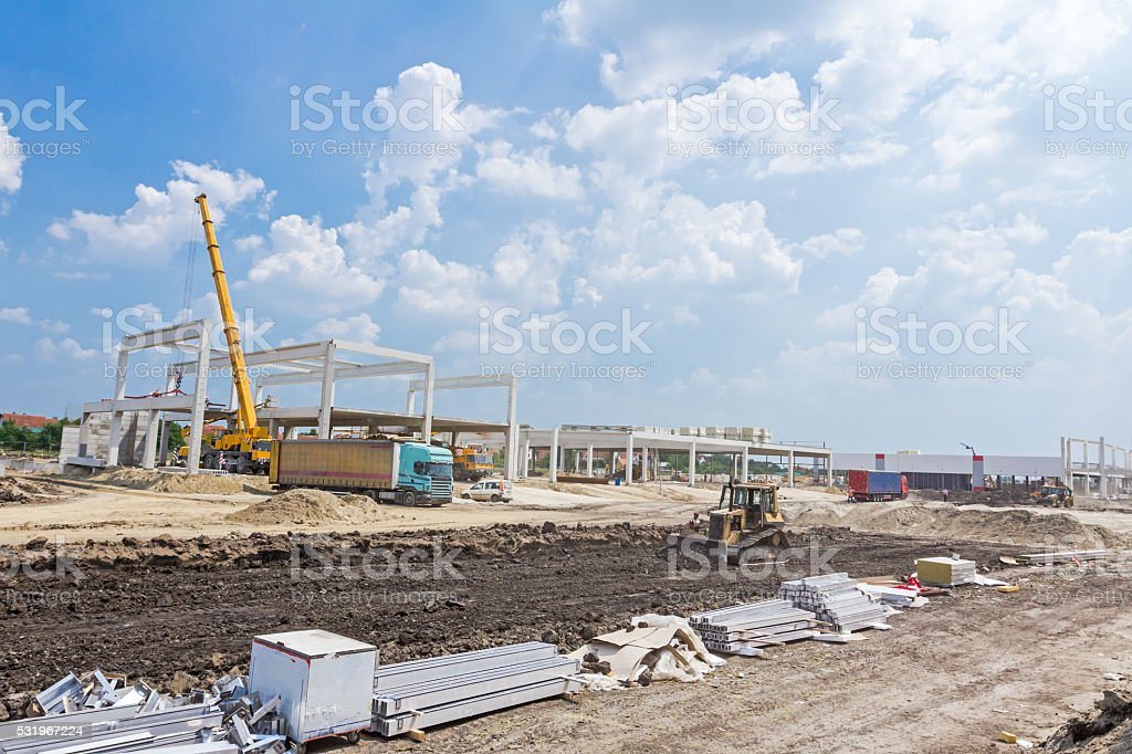 Mobile crane is unloading concrete joist from truck trailer. stock photo