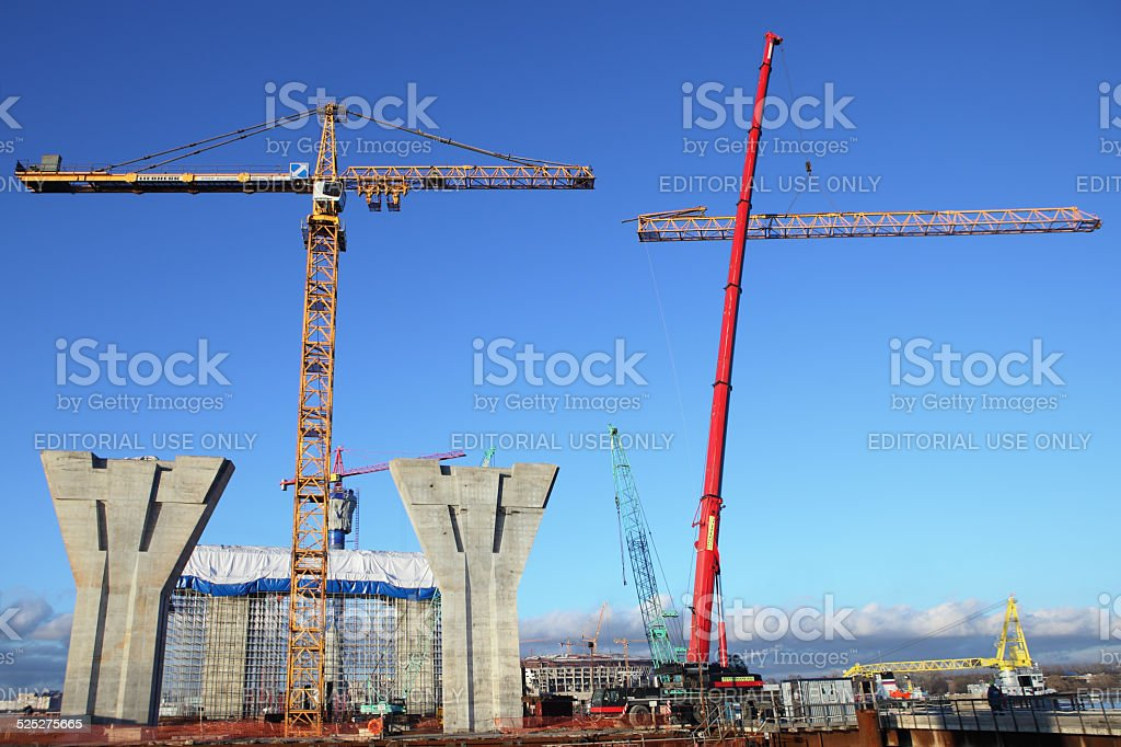 Mobile crane lifts up a section of the tower crane. stock photo