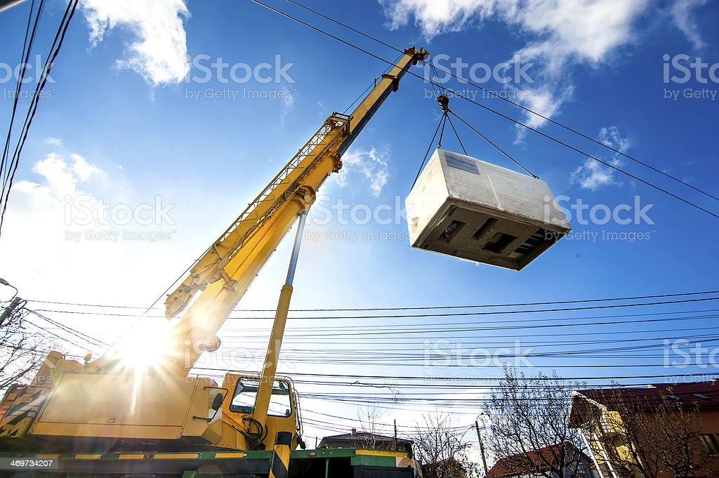 Mobile crane operating by lifting and moving electric generator stock photo