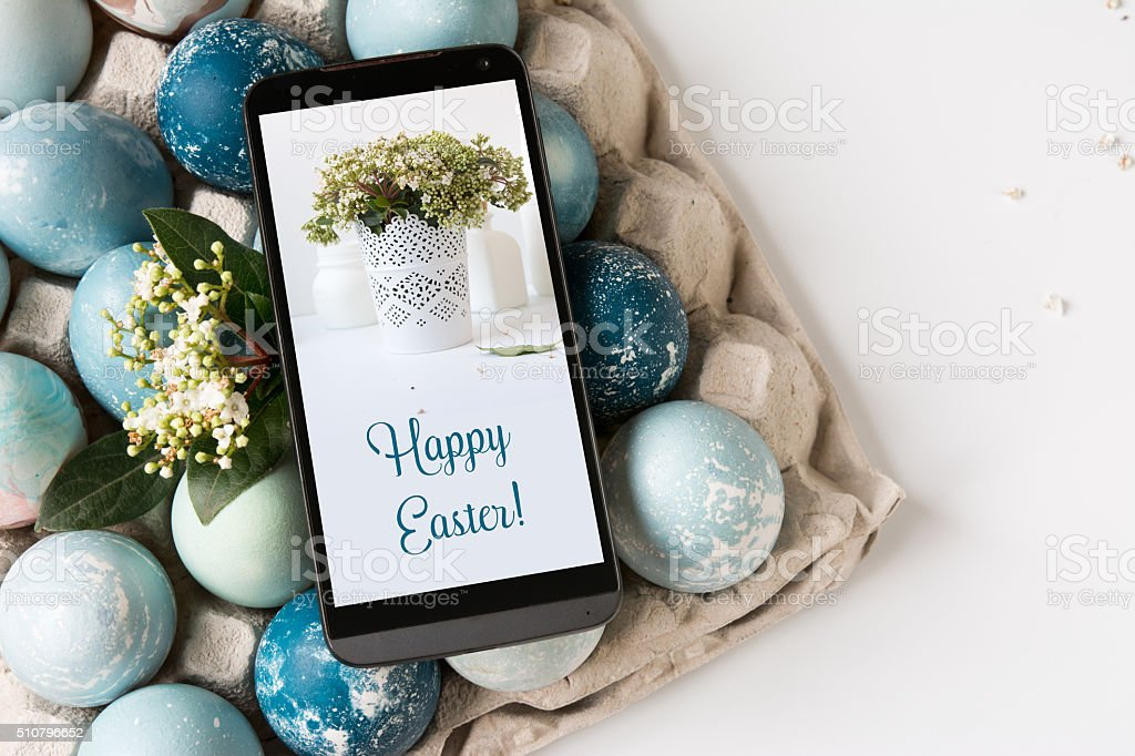 Mobile Easter card on the screen, decorative eggs on blue stock photo