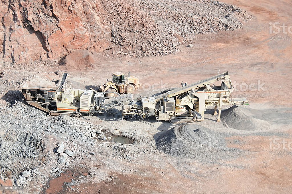 mobile jaw plant in Open-pit Mine with Earth Mover stock photo