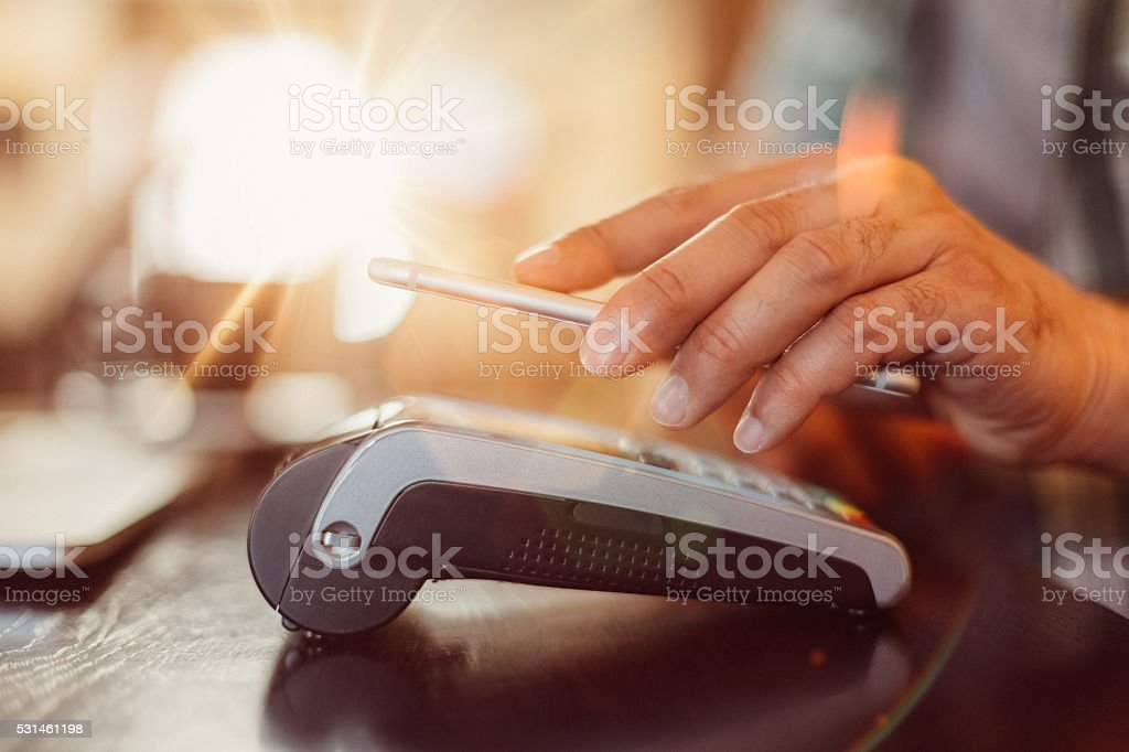 Mobile payment in a cafe stock photo